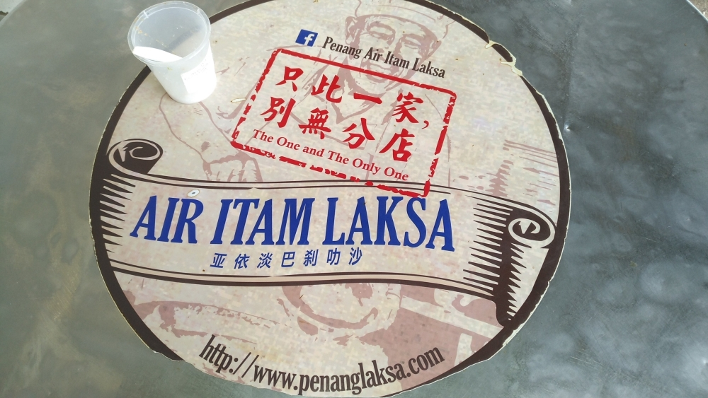 Air Itam Laksa sticker logo on your table, with a plastic cup of salt if need to flavour your laksa